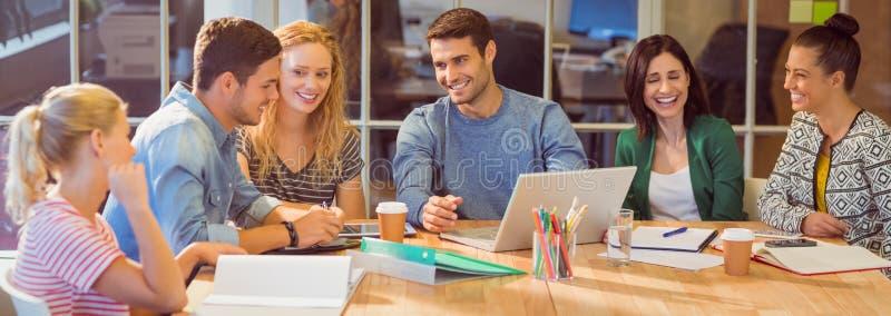 Grupp av unga kollegor som använder bärbara datorn arkivfoto