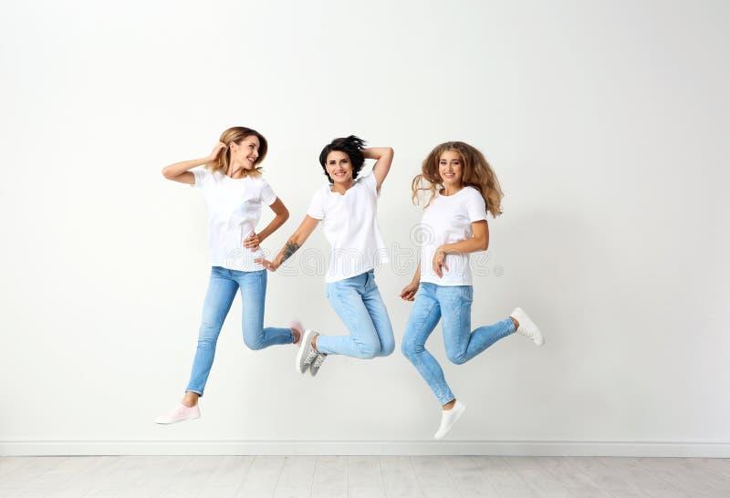 Grupp av unga kvinnor, i att hoppa för jeans royaltyfri bild