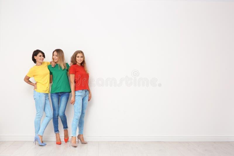 Grupp av unga kvinnor i jeans och färgrika t-skjortor arkivbild
