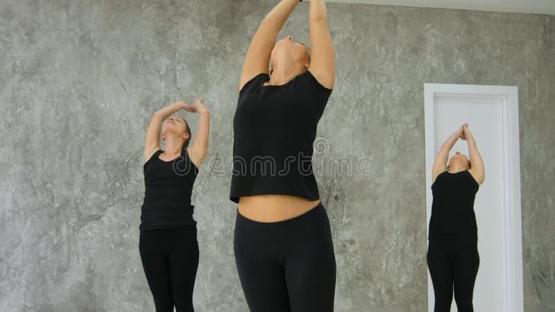 Grupp av unga kvinnor som avslutar asanaen, praktiserande yoga arkivfoto