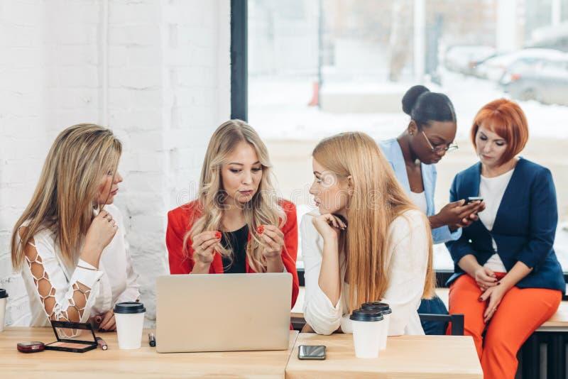Grupp av unga kvinnor som diskuterar idérikt projekt under arbetsprocess royaltyfri bild
