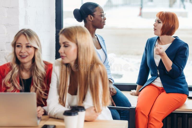 Grupp av unga kvinnor som diskuterar idérikt projekt under arbetsprocess royaltyfri foto