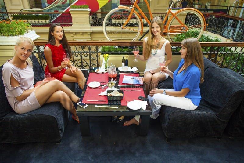 Grupp av unga kvinnor som sitter runt om tabellen som äter efterrätten fotografering för bildbyråer