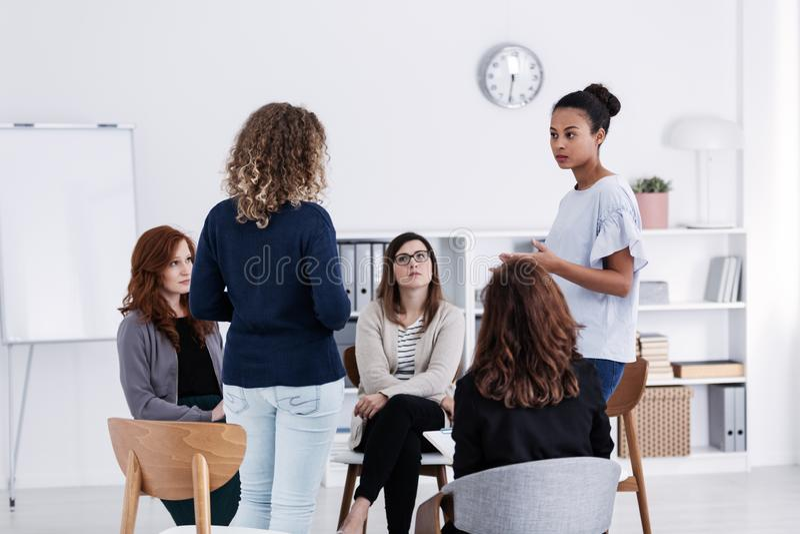 Grupp av unga kvinnor som talar sammanträde i en cirkel arkivfoton