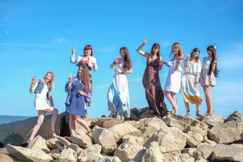 Grupp av unga kvinnors anseende tillsammans på en strand på en sommardag Lyckliga ungdomarsom tycker om en dag på stranden royaltyfri foto