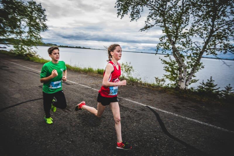 Grupp av unga löpare och ungar som tillsammans springer arkivbild