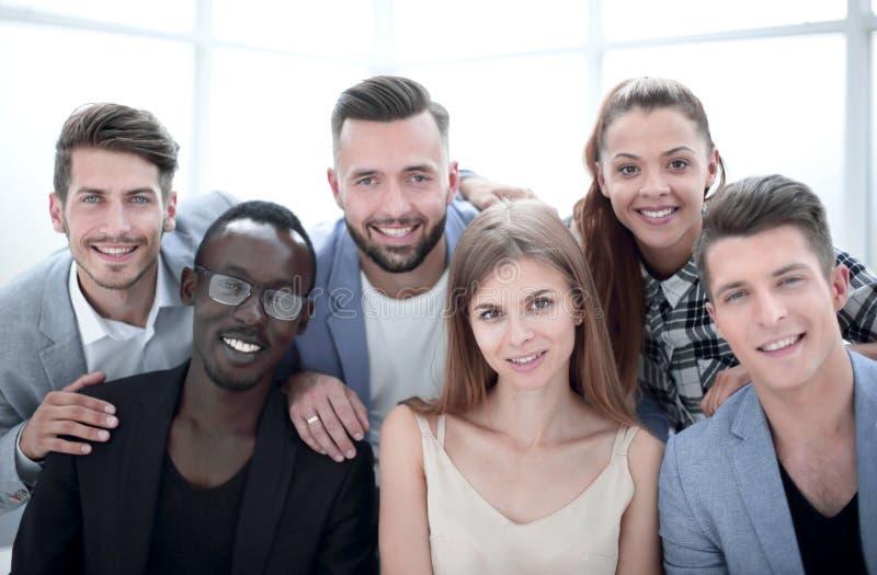 Grupp av unga ledare som ler på kameran under ett arbetsmöte arkivbild