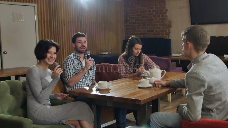 Grupp av unga lyckliga vänner som har gyckel på karaoke och att sjunga och att ta selfie som dricker te royaltyfria foton