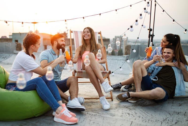 Grupp av unga lyckliga vänner som har partiet och gyckel arkivfoto