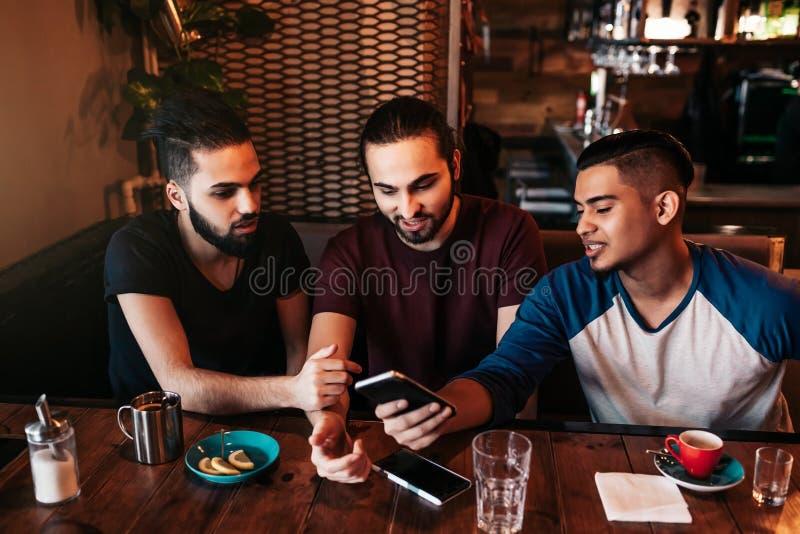 Grupp av unga män för blandat lopp som använder telefonen och talar i vardagsrumstång Blandras- vänner som har gyckel i kafé royaltyfria bilder