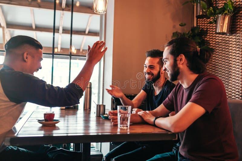 Grupp av unga män för blandat lopp som talar i vardagsrumstång Blandras- vänner som har gyckel i kafé royaltyfri bild