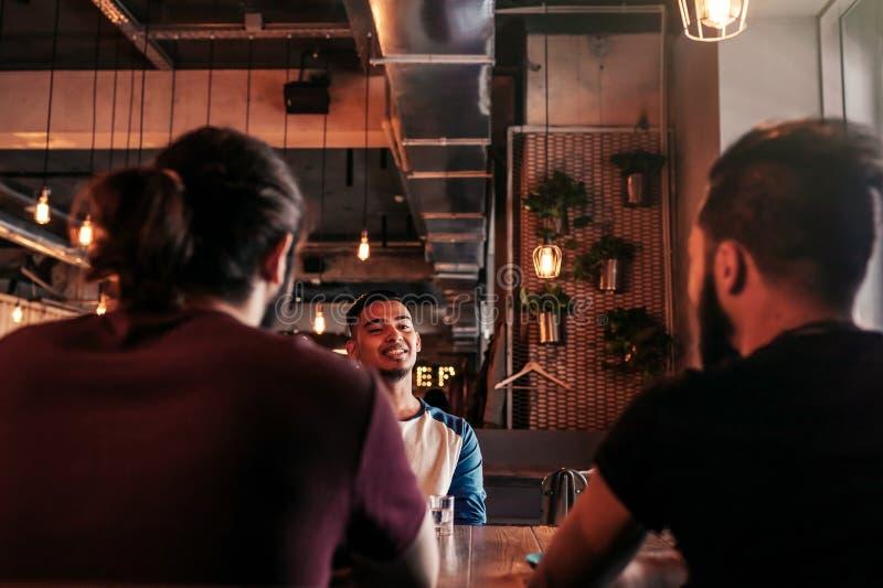 Grupp av unga män för blandat lopp som talar och skrattar i vardagsrumstång Blandras- vänner som har gyckel i kafé Grabbar hänger royaltyfria foton