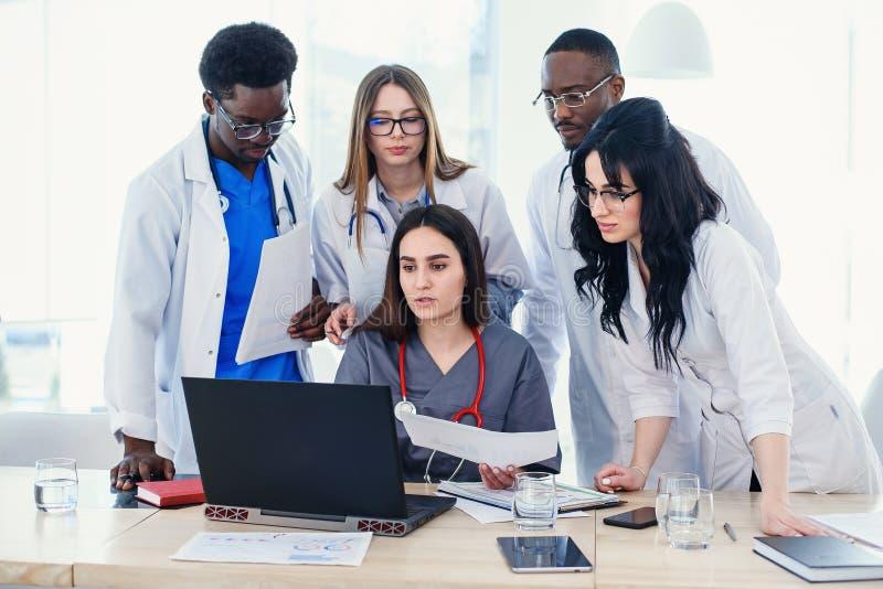 Grupp av unga m?ng- nationella doktorer under att arbeta med b?rbara datorn i konferensrummet royaltyfri bild