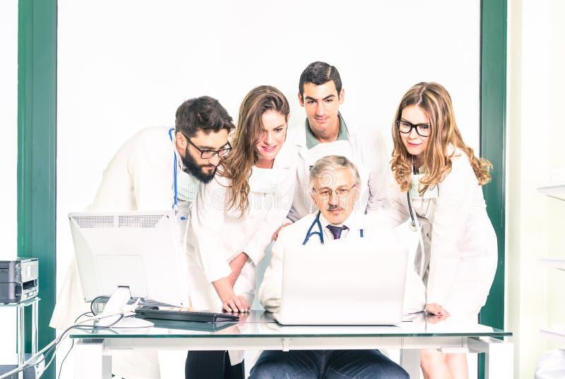Grupp av unga medicinstudenter med den höga doktorn på kliniken arkivfoto