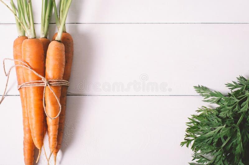 Grupp av unga morötter med grön blast på den vita trätappningtabellen, sund mat på åtlöje upp bästa sikt för bakgrund royaltyfria foton