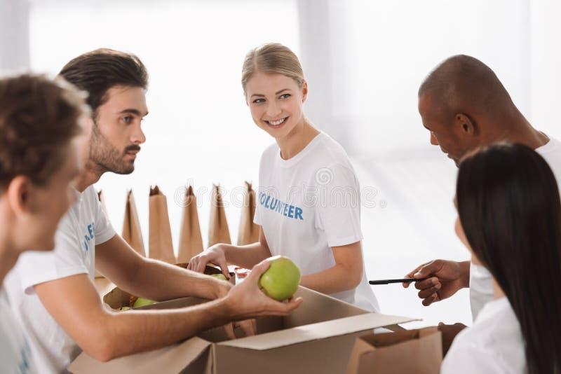grupp av unga multietniska volontärer som packar mat royaltyfri foto