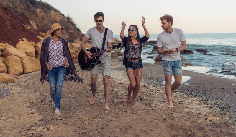 Grupp av unga och gladlynta vänner som går på stranden arkivfoto
