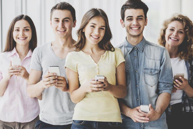 Grupp av unga positiva vänner som rymmer telefoner fotografering för bildbyråer