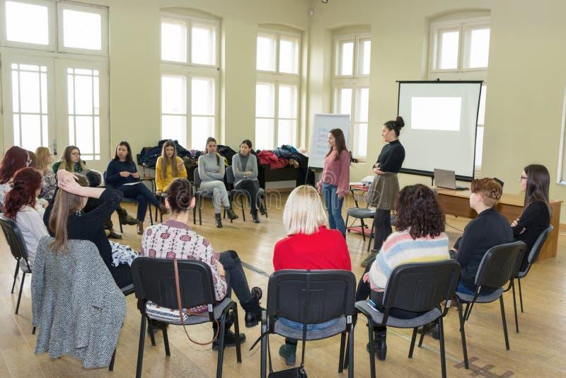 Grupp av unga universitetsstudenter som har en gruppdiskussion som tillsammans sitter på en cirkel av stolar och samtal arkivfoto