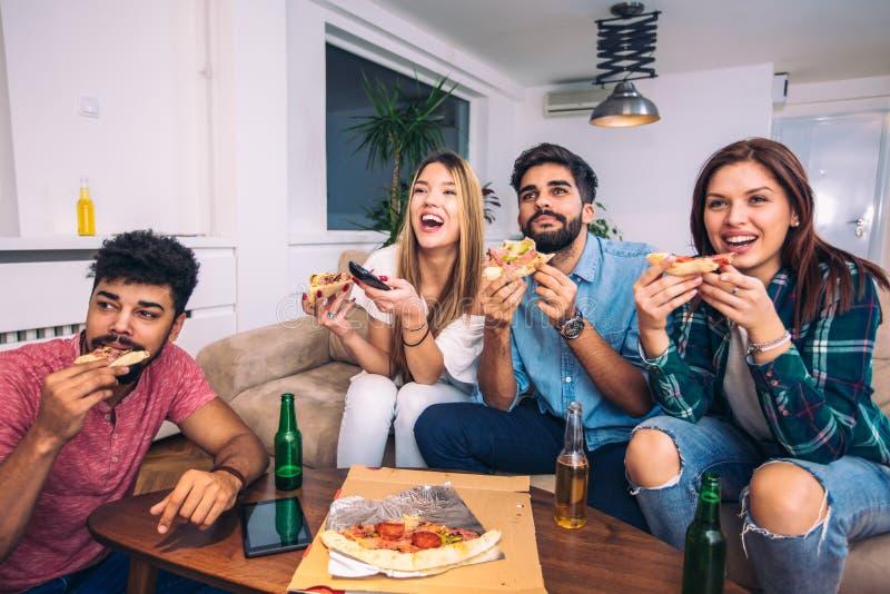 Grupp av unga vänner som äter pizza och håller ögonen på tv arkivfoto