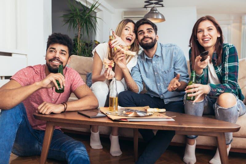 Grupp av unga vänner som äter pizza och håller ögonen på tv royaltyfri bild