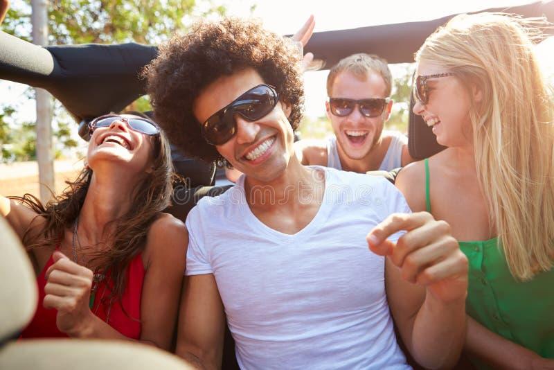 Grupp av unga vänner som dansar i baksida av den öppna bästa bilen fotografering för bildbyråer