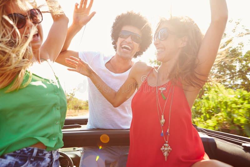 Grupp av unga vänner som dansar i baksida av den öppna bästa bilen arkivbilder