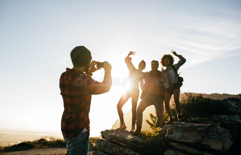 Grupp av unga vänner som fotvandrar på berget royaltyfria foton