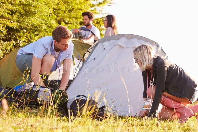 Grupp av unga vänner som kastar tält på campa ferie royaltyfria bilder