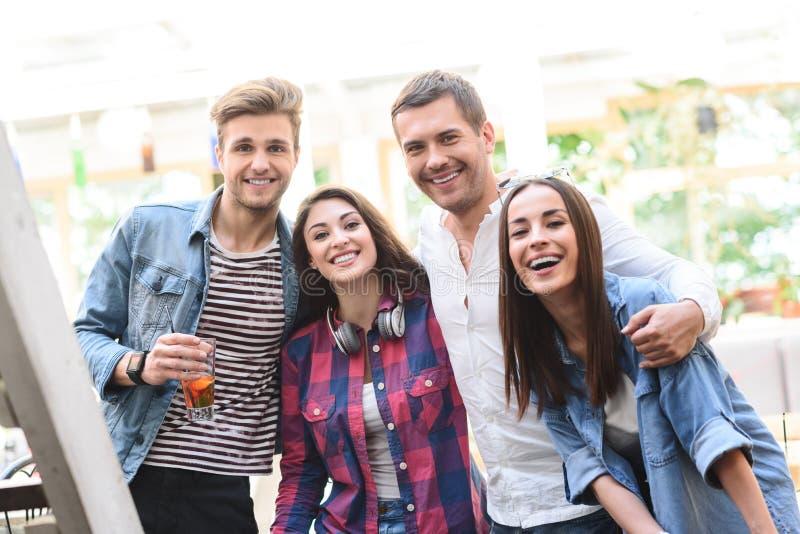 Grupp av unga vänner som möter i kafé arkivfoton