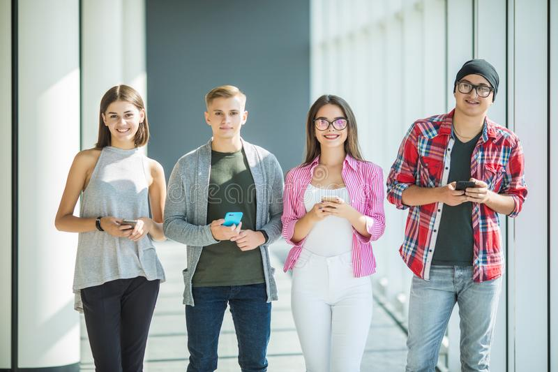 Grupp av unga vänner som ser deras smarta telefoner, utan växelverkan inomhus Begrepp av livsstilen, teknologier a royaltyfri bild