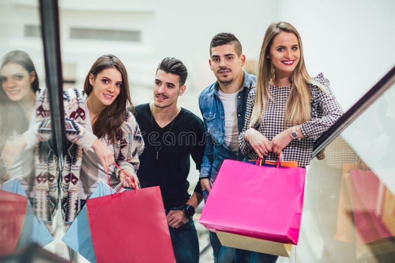 Grupp av unga vänner som shoppar i galleria arkivfoto