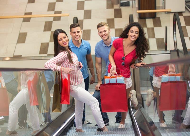 Grupp av unga vänner som shoppar i galleria arkivbilder