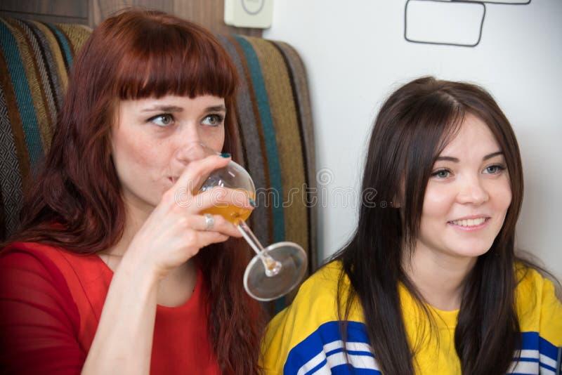 Grupp av unga vänner som sitter i kafé En kvinna som har en drink arkivfoto