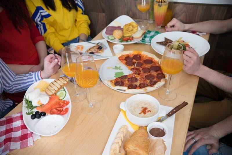 Grupp av unga vänner som sitter i kafé en tabell mycket av mat arkivfoto
