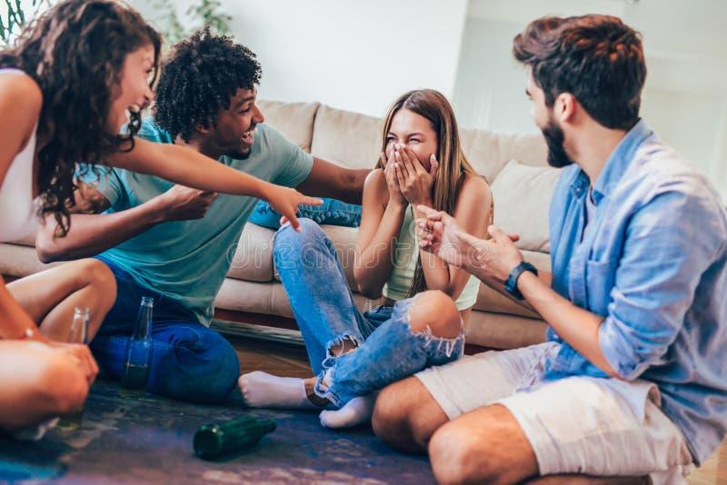 Grupp av unga vänner som spelar leken av sanning royaltyfri bild