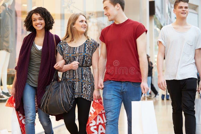 Grupp av unga vänner som tillsammans shoppar i galleria arkivfoton