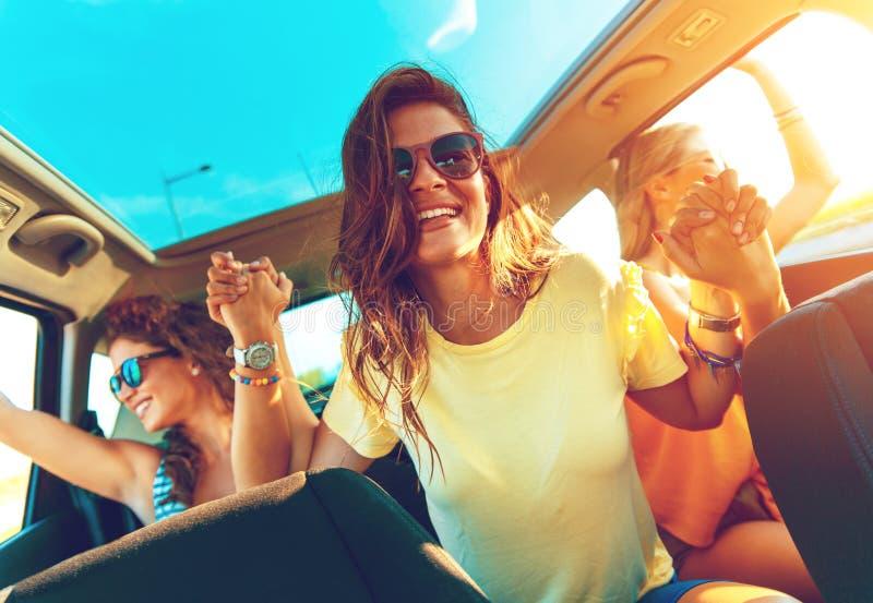 Grupp av unga vänner som tycker om en dag på sjön Tre kvinnliga vänner som tycker om att resa i bilen royaltyfri fotografi