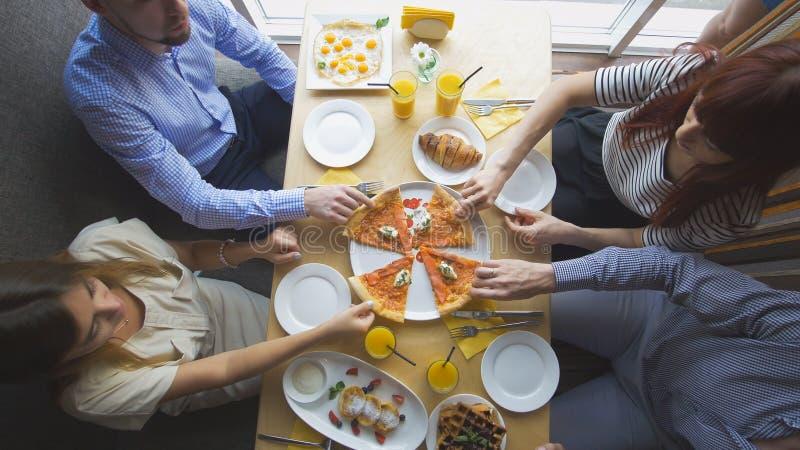 Grupp av unga vänner som tycker om en matställe som talar under att äta pizza royaltyfri foto