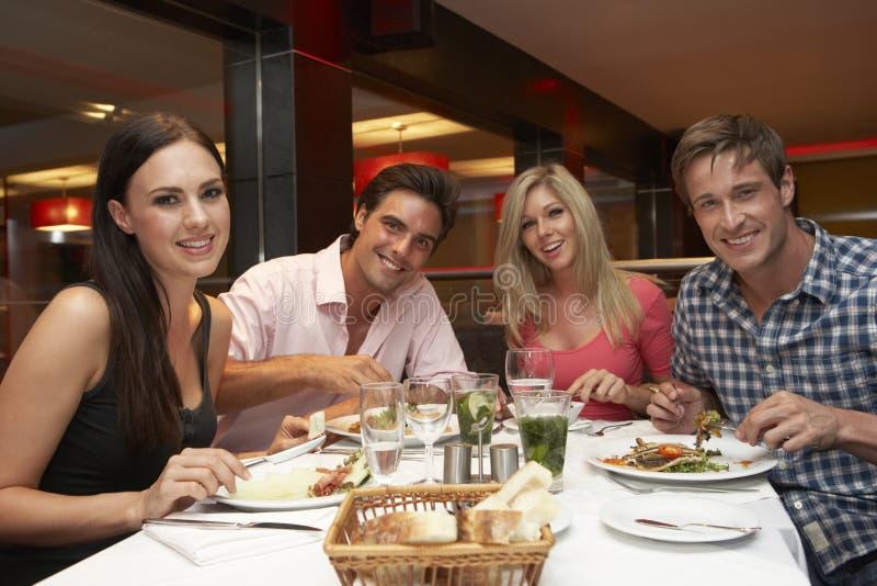 Grupp av unga vänner som tycker om mål i restaurang arkivfoto