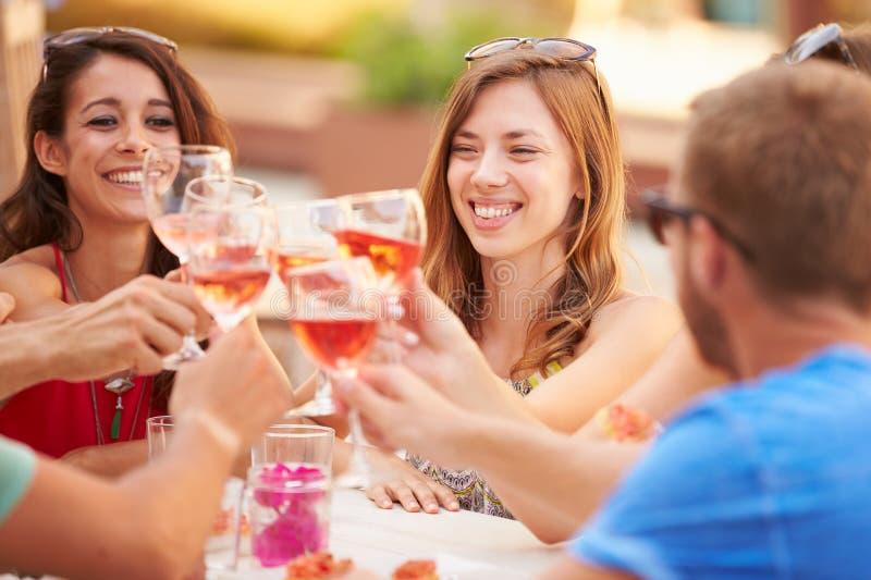 Grupp av unga vänner som tycker om mål i utomhus- restaurang arkivfoto
