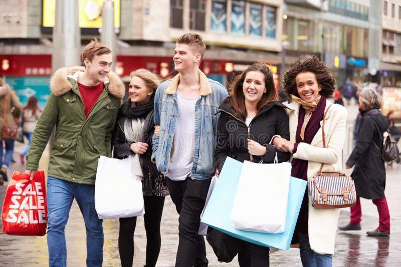 Grupp av unga vänner som utomhus tillsammans shoppar royaltyfri foto
