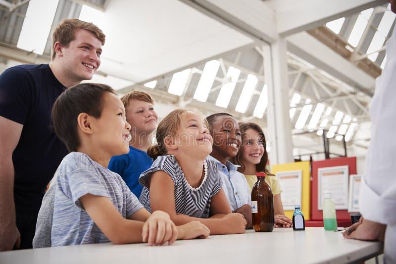 Grupp av ungar med lärare som har gyckel på en vetenskapsmitt royaltyfri bild