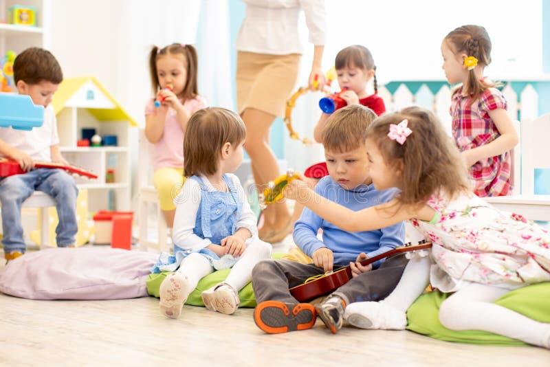 Grupp av ungar med musikinstrument i daycare fotografering för bildbyråer