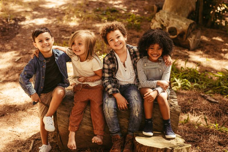 Grupp av ungar på en träjournal arkivbild