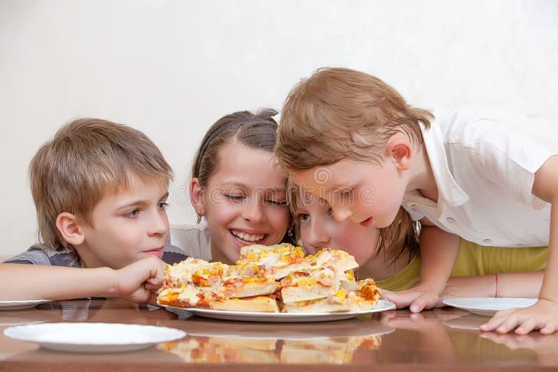 Grupp av ungar som äter pizza och att le royaltyfri bild