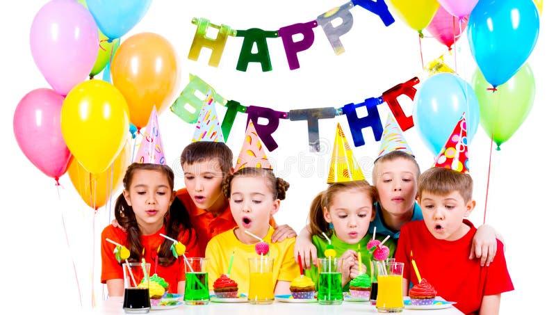 Grupp av ungar som blåser stearinljus på födelsedagpartiet royaltyfri bild