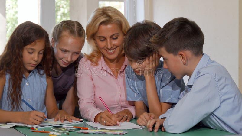 Grupp av ungar som håller ögonen på deras teckning för konstlärare under grupp arkivbild