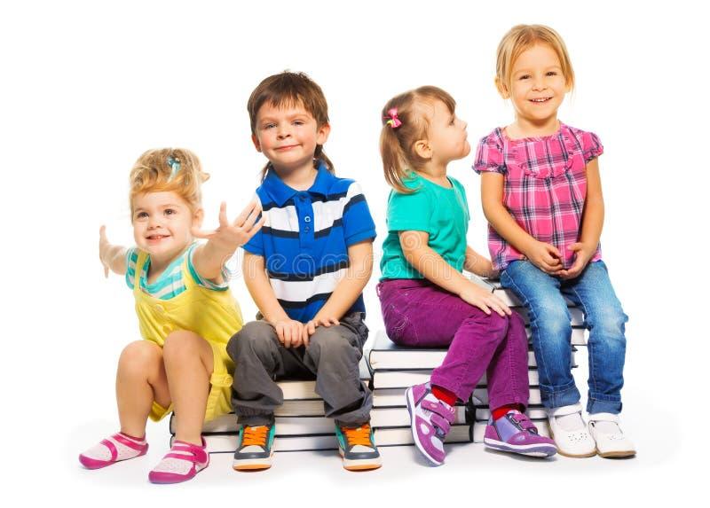 Grupp av ungar som sitter på bokbunten royaltyfri bild