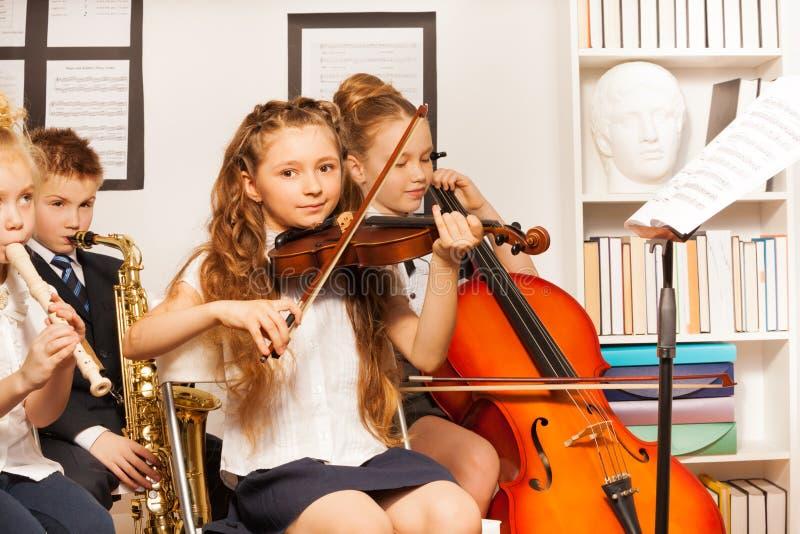 Grupp av ungar som spelar musikinstrument inomhus royaltyfri fotografi